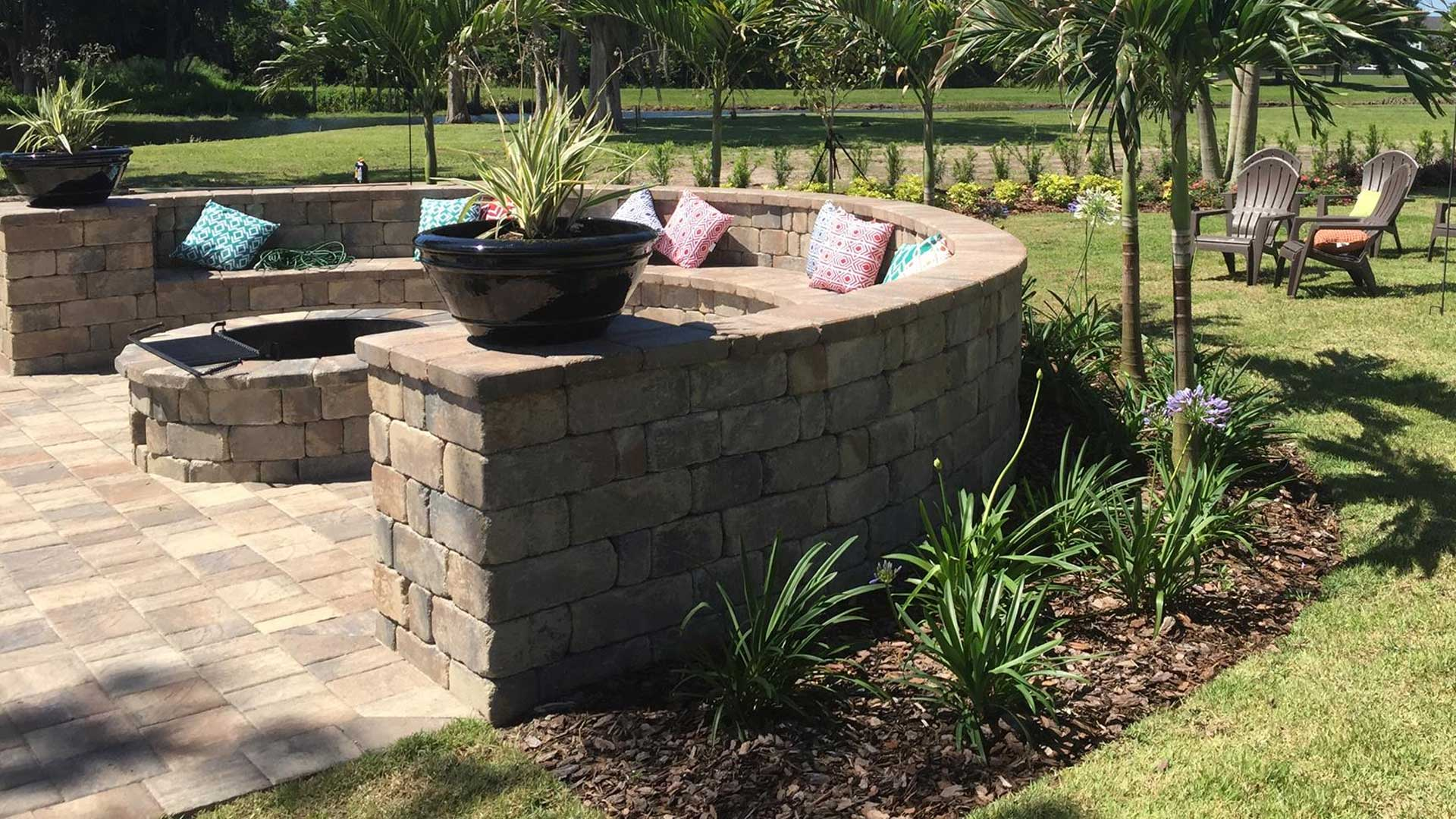 A fire pit with a seating wall around it and a paver patio that we recently installed in Winter Garden..