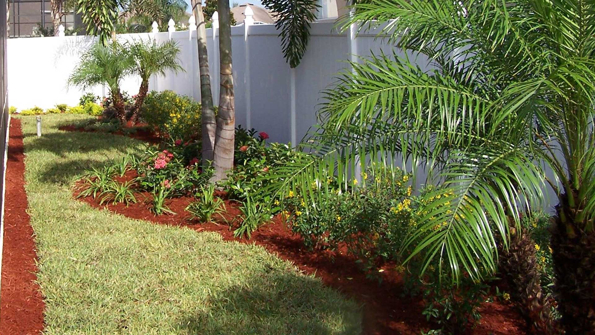 Red mulch laid in a new landscaping bed around a property located in The Villages, FL.